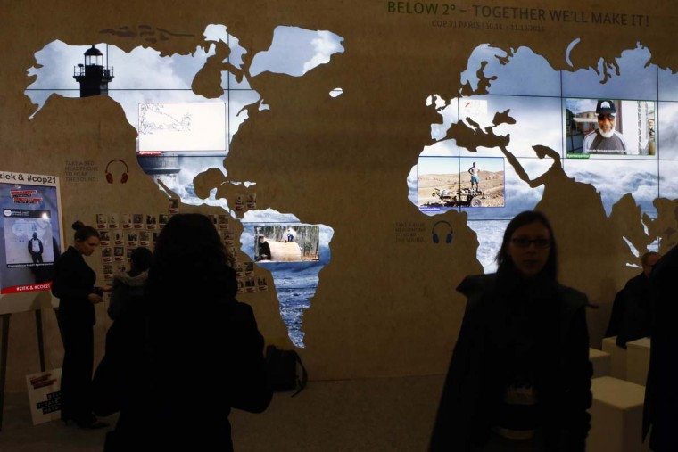 "People pass a world map at The German pavillon entitled ""Below 2 degrees, Together we'll make it"" during the COP21, United Nations Climate Change Conference, in Le Bourget, north of Paris, Thursday, Dec. 3, 2015. Many protesters in Paris were  silenced by a demonstration ban this week, though some found creative measures around the edict.  