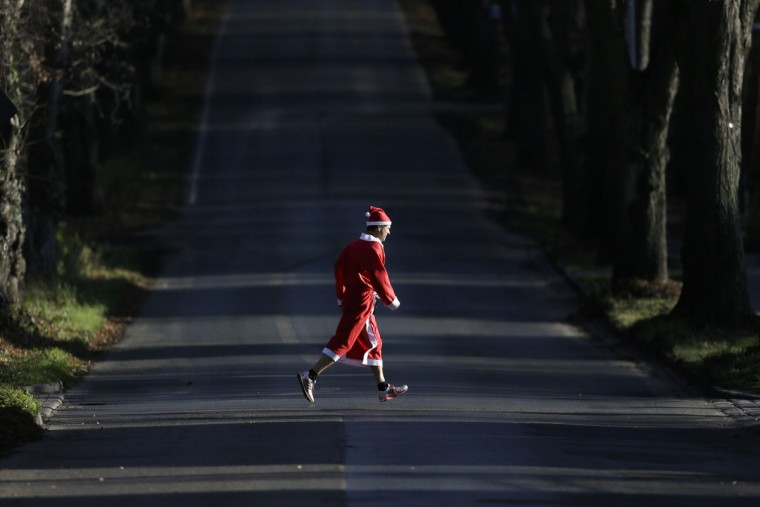 A man dressed as Santa Claus crosses a street on his way to take part in the Santa Claus run in Michendorf 43 kilometers ( about 27 miles) south east of Berlin, Germany, Sunday, Dec. 6, 2015. (AP Photo/Markus Schreiber)