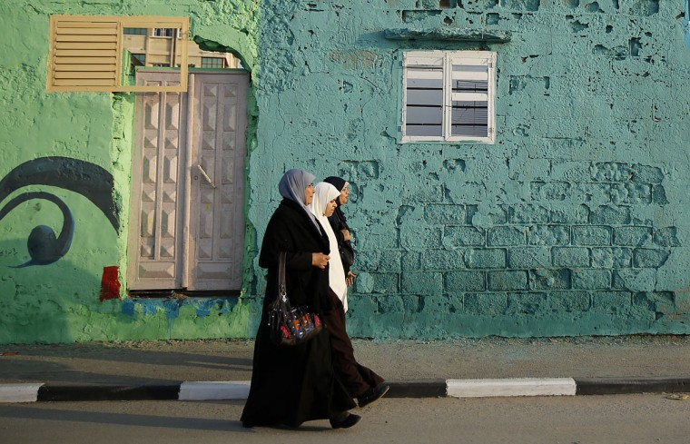 In this Saturday Dec. 19, 2015 photo, a Palestinian walk past a painted house in the Shati refugee camp in Gaza City. Shatihas always been a symbol of poverty, a grey concrete jungle with 87,000 people packed into one fifth of a square mile (half a square kilometer). But now, overlooking the sewage-contaminated Mediterranean beachfront, the campís houses are covered in vibrant colors. (AP Photo/Hatem Moussa)