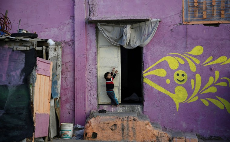 In this Saturday Dec. 19, 2015 photo, a Palestinian boy hangs on a door of his home that was painted by artists in the Shati refugee camp in Gaza City. ìItís a voluntary work to bring joy and happiness for our families and children in the Shati camp,î said Mohammed Dahman, a painter who worked for a month on the project. (AP Photo/Hatem Moussa)