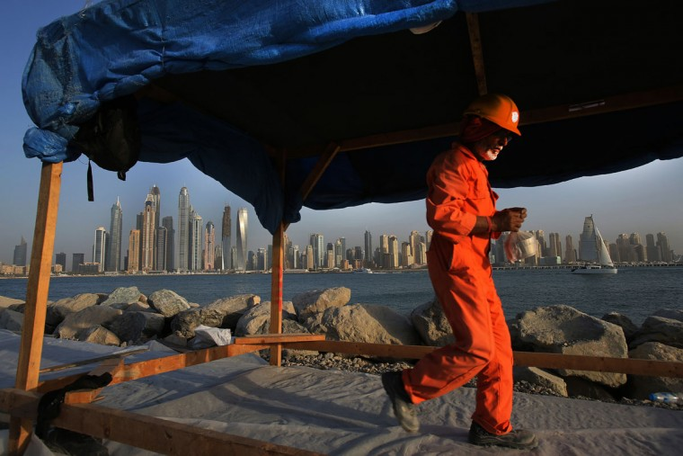 In this Sept. 22, 2015 photo, a laborer carries his lunchbox as he leaves a construction site for the day at the Palm Jumeirah opposite the Marina district, in Dubai, United Arab Emirates. Armies of low-paid migrant workers, many of them from the Indian Subcontinent, leave behind families and travel to Dubai to build soaring towers like those in the Marina. While the wages they come for offer hope of a better life, they are far too meager for most to ever dream of calling the Marina they built home. (AP Photo/Kamran Jebreili)