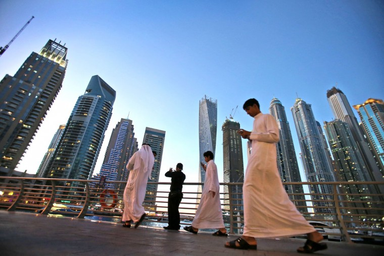 "In this April 1, 2015 photo, Gulf Arab visitors in their traditional ""Kandora"" pass by giant skyscrapers at the Marina waterfront in Dubai, United Arab Emirates. The area is sometimes referred to as the Manhattan of the Middle East and some of its buildings are promoted by realtors as having ""Manhattan-style"" architecture. Penthouses in the Dubai Marina are similarly priced to New York City''s upscale properties. (AP Photo/Kamran Jebreili)"