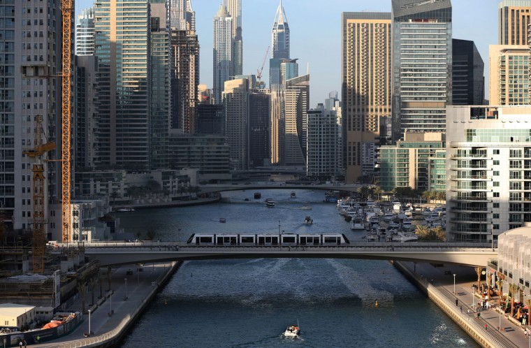 In this April 1, 2015 photo, a tram crosses a bridge over a canal that forms the Marina waterfront district of Dubai, United Arab Emirates. The Marina neighborhood is one of many clusters of neck-bending skyscrapers built throughout Dubai, but its real power lies behind the gated privacy of its most luxurious towers. Owning an apartment in one of these towers means access to skyline pools, concierge services and grand apartments that cater to the region's royalty, as well as the world''s wealthiest businessmen and women. (AP Photo/Kamran Jebreili)
