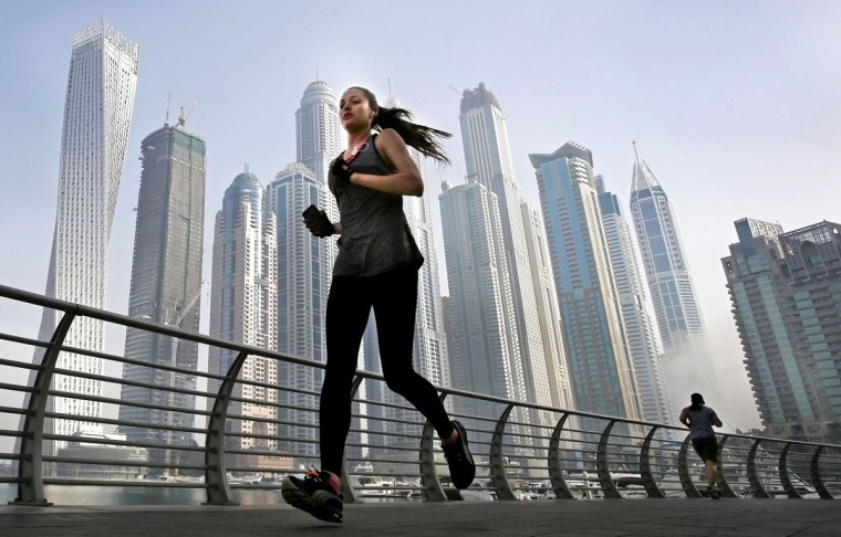 In this April 9, 2015 photo, as the early morning fog lifts, a woman jogs in front of giant skyscrapers at the Marina waterfront in Dubai, United Arab Emirates. Dubai''s rapid transformation from a desert outpost into one of the world''s most architecturally stunning cities is mapped out in Marina. Where just 15 years ago there was empty, flat land, today a bustling neighborhood thrives centered around a canal and an impressive skyline. (AP Photo/Kamran Jebreili)