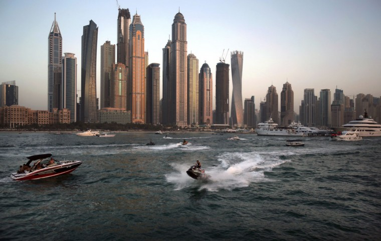 In this Friday, April 10, 2015 photo, people use recreational vehicles opposite the Marina district of Dubai, United Arab Emirates. Dubai''s year-round sunshine gives Marina a summer-vibe throughout the winter months, when temperatures rarely drop below a comfortable 75 degrees Fahrenheit (24 Celsius) during the day. On weekends, alcohol-fueled party boats ferry Russian and Western expatriates down the canal as speed boats and jet skis come out for a ride. (AP Photo/Kamran Jebreili)