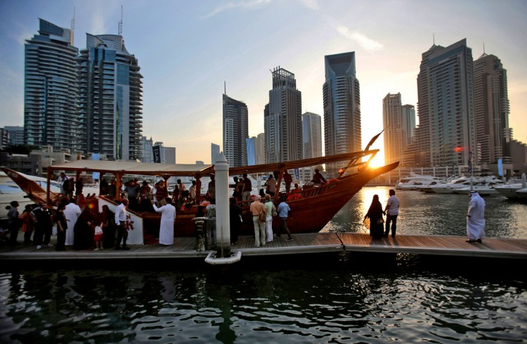 In this March 25, 2015 photo, tourists of different nationalities board a dhow for a cruise as the sun sets in the Marina neighborhood of Dubai, United Arab Emirates. Dubai''s year-round sunshine gives the Marina a summer-vibe throughout the winter months, when temperatures rarely drop below a comfortable 75 degrees Fahrenheit (24 Celsius) during the day. (AP Photo/Kamran Jebreili)