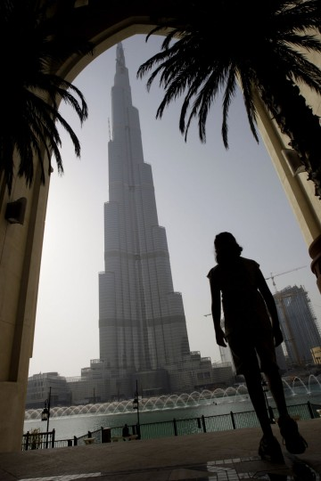 A young woman looks at the Burj Dubai, the world's tallest tower in Dubai, United Arab Emirates, Monday, July 13, 2009. (AP Photo/Kamran Jebreili)