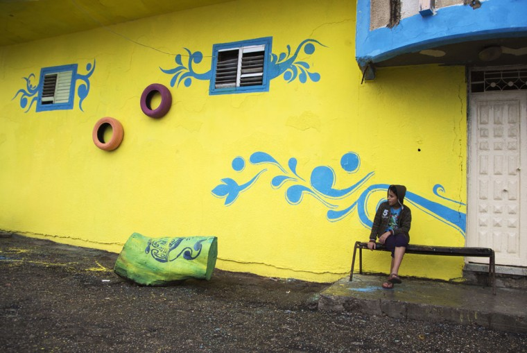 "A Palestinian boy sits outside his family house that was painted by Palestinian artists in the al-Shati Refugee Camp in Gaza City, Tuesday, Nov. 17, 2015. More than 30 artists took part in the ""Gaza More Beautiful"" project funded by Padico Holding, a leading investment and development company in the Palestinian Territories. (AP Photo/Adel Hana)"