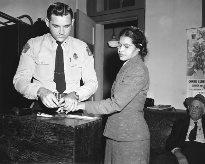 In this  Feb. 22, 1956, file photo, Rosa Parks, whose refusal to move to the back of a bus touched off the Montgomery bus boycott, is fingerprinted by police Lt. D.H. Lackey in Montgomery, Ala. She was among some 100 people charged with violating segregation laws. (Gene Herrick/AP)