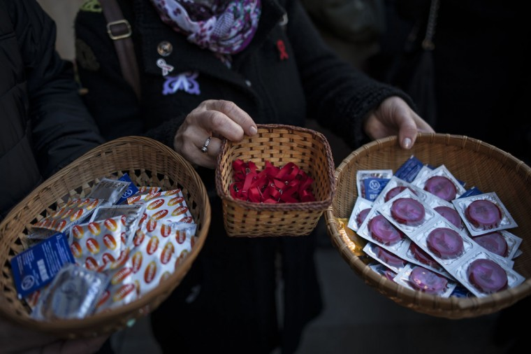 A woman holds baskets with reds ribbon symbol of the fight against AIDS, center, and prophylactics during a demonstration on the World Aids Day, in Pamplona northern Spain, Tuesday, Dec. 1, 2015. (AP Photo/Alvaro Barrientos)