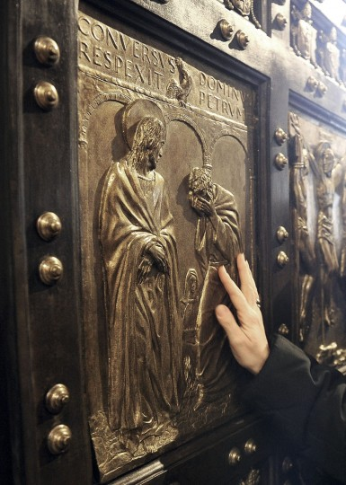 A woman touches the Holy Door of St. Peter's Basilica, at the Vatican, Tuesday, Dec. 8, 2015. Pope Francis pushed open the great bronze doors of St. Peter's Basilica on Tuesday to launch his Holy Year of Mercy, declaring that mercy trumps moralizing in his Catholic Church. (Maurizio Brambatti/ANSA via AP)
