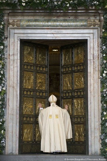 Pope Francis pushes open the Holy Door of St. Peter's Basilica, formally launching the Holy Year of Mercy, at the Vatican, Tuesday, Dec. 8, 2015. Francis stood in prayer on the threshold of the basilica's Holy Door then walked through it, the first of an estimated 10 million faithful who will pass through over the course of the next year in a rite of pilgrimage dating back centuries. (L'Osservatore Romano/Pool Photo via AP)