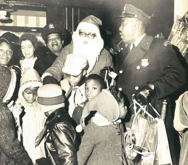 """Children in the Western Police District gather around Santa at the annual Christmas party at the Royal Theater. Patrolman Nathaniel Ponder, of the Western District, helps distribute stockings filled with """"goodies"""" as the children leave. (Baltimore Sun, 1962)"""