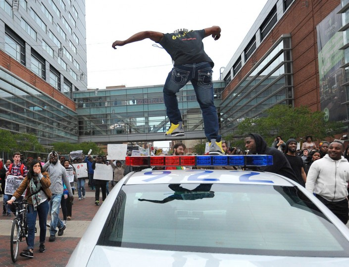 A person jumps on top of a police car during a Saturday March and rally related to the death of Freddie Gray. (Kim Hairston/Baltimore Sun)