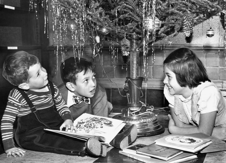 Listening to the tintinnabulation of the bells on the musical Christmas tree at the Enoch Pratt Library in 1950 are (from left) Roddy Freeman, 2; Thomas Beach, 8, and Carole Ann Beach, 9.  (William Klender/Baltimore Sun)