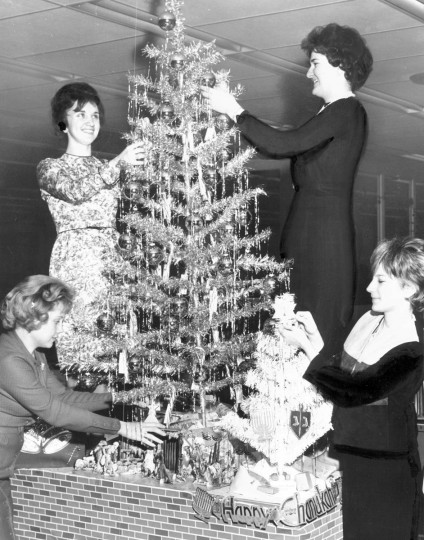 Social Security workers decorate a Christmas tree and a Hanukkah bush during traditional Christian and Jewish holiday seasons in 1962.  From left are the Misses Mary Zimnawoda, Bonnie Worth and Mary Erisini and Mrs. Bryna Dannenberg.  (Edward Nolan/Baltimore Sun)
