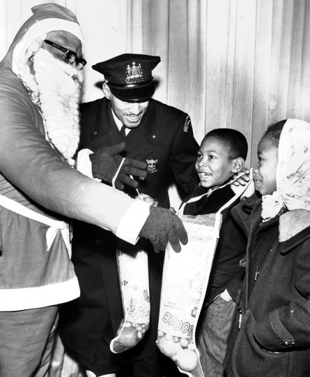 "Creston ""Doc"" Woingust, dressed as one of Santa's helpers, and patrolman Alfred C. Smith, give stockings to a brother and sister, Everett, 8, and Wanda Loggins, 7, at the 1963 Western District Christmas party that was held at the old Royal Theater on Pennsylvania Avenue. (William l Laforce Jr./Baltimore Sun)"