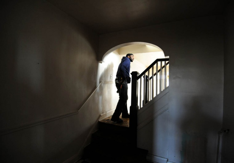 David Johnson, Jr., laborer, Department of Public Works, walks through a house at 3249 Shannon Drive. He is checking for squatters and animals before boarding up the vacant property. (Kim Hairston/Baltimore Sun)