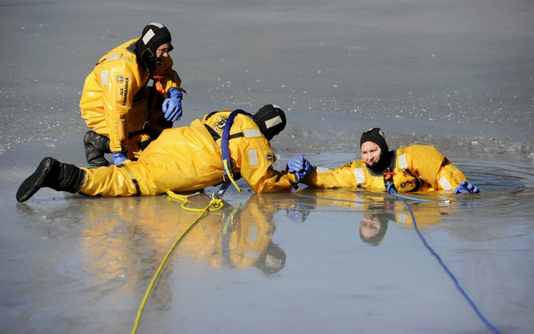 "Steve Colburn, Howard County firefighter, paramedic, reaches for ""victim"" and fellow firefighter Ashley Bayse, as they drill under the watch of Capt. Michael Sharpe. The members of Howard County Fire and Rescue Services Station 7 performed ice rescue training drills on the frozen lake at Centennial Park in Clarksville. (Christopher T. Assaf, Baltimore Sun)"