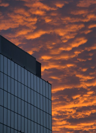 The Hyatt hotel reflects a northern blue sky as clouds from the western area are bathed in the colors of sunset during the arrival of Santa Claus at the inner harbor Ampitheater at Harborplace Saturday, Nov. 23, 2013. (Karl Merton Ferron/Baltimore Sun)