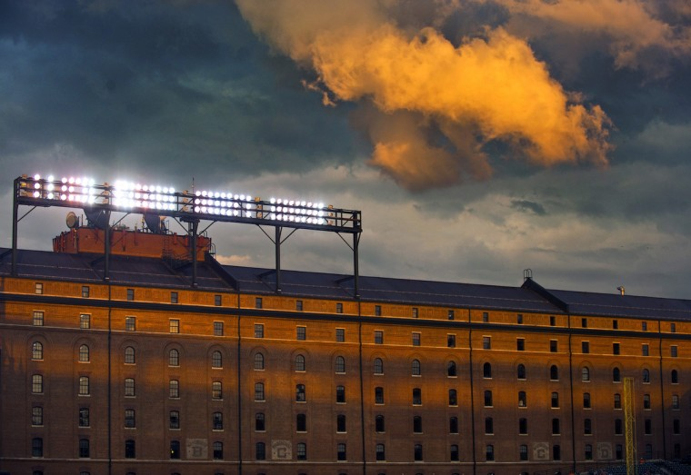 The evening sun casts orange against the clouds that float above the Eutaw Street warehouse during a game against the Baltimore Orioles, who host the Oakland Athletics at Oriole Park at Camden Yards Saturday, Jul 28, 2012. (Karl Merton Ferron/Baltimore Sun)