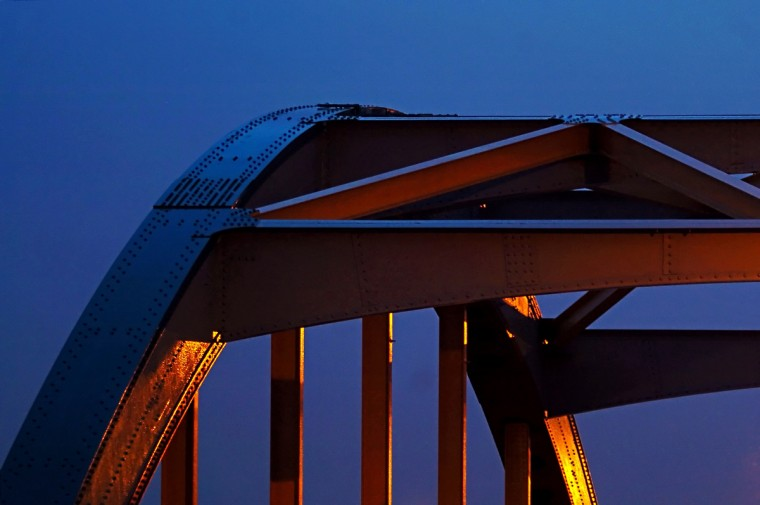 "The Guilford Avenue Bridge is illuminated by the orange glow of street lamps, blended with the cool cerulean dusk as twilight fades to darkness following a heavy rain Monday, March 28, 2005. The Guilford Avenue Bridge is listed as an historic bridge in Maryland's SHA (State Highway Administration) website. According to the site, SHA teamed with Maryland Historical Trust and the Federal Highway Administration, taking inventory of bridges still in existence in Maryland, for SHA's cultural resources initiative. The metal arch bridge, constructed in 1936 is currently listed as an ""historic resource,"" one of 415 bridges in the state listed in the National Register. (Karl Merton Ferron/Baltimore Sun)"