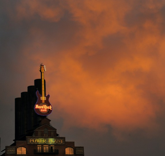 The Power Plant building and Hard Rock Cafe sign glow beneath clouds hit by vibrant shades of a sunset during a protest that started outside Baltimore City Hall in 2014. (Karl Merton Ferron/Baltimore Sun)