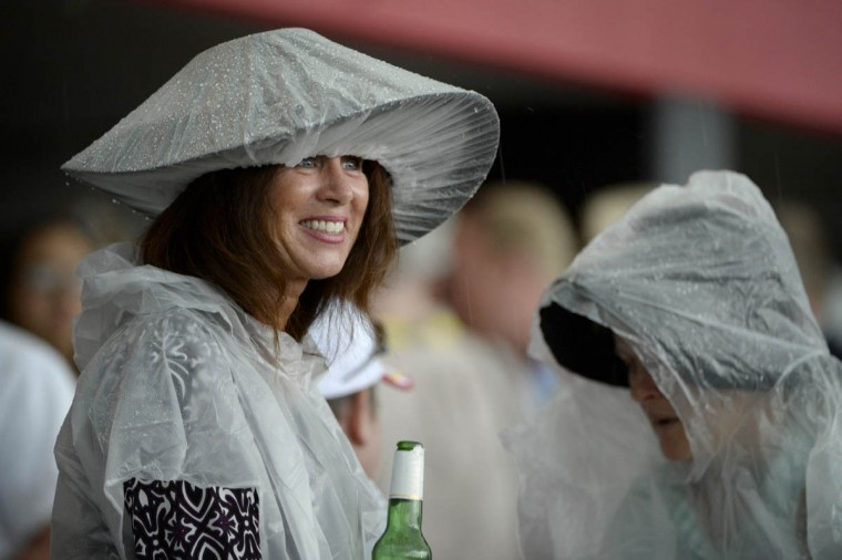 The rain doesn't dampen the spirit of one race spectator, nor her hat, as the weather changed quickly before the 140th running of the Preakness Stakes at Pimlico. (Christopher T. Assaf, Baltimore Sun)