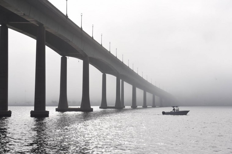 A fisherman passes under a fog-shrouded Naval Academy Bridge. ( Jerry Jackson/ Baltimore Sun)