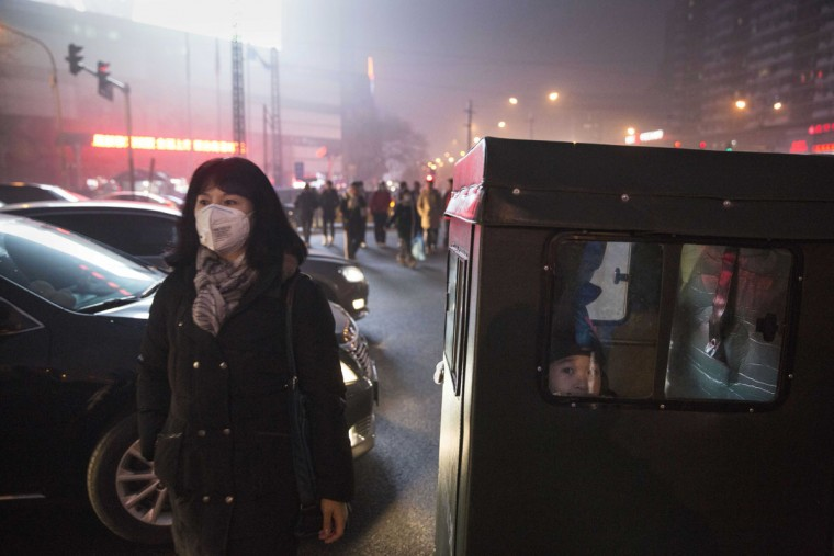 A Chinese woman wears a mask as protection from the pollution crosses a road on December 1, 2015 in Beijing, China. (Photo by Kevin Frayer/Getty Images)