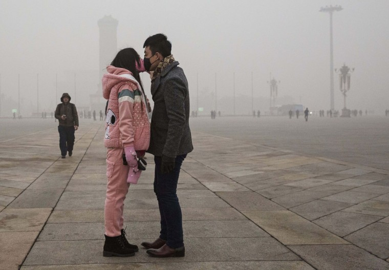 A Chinese couple wear masks as they kiss during a day of high pollution in Tiananmen Square on December 1, 2015 in Beijing, China. (Photo by Kevin Frayer/Getty Images)
