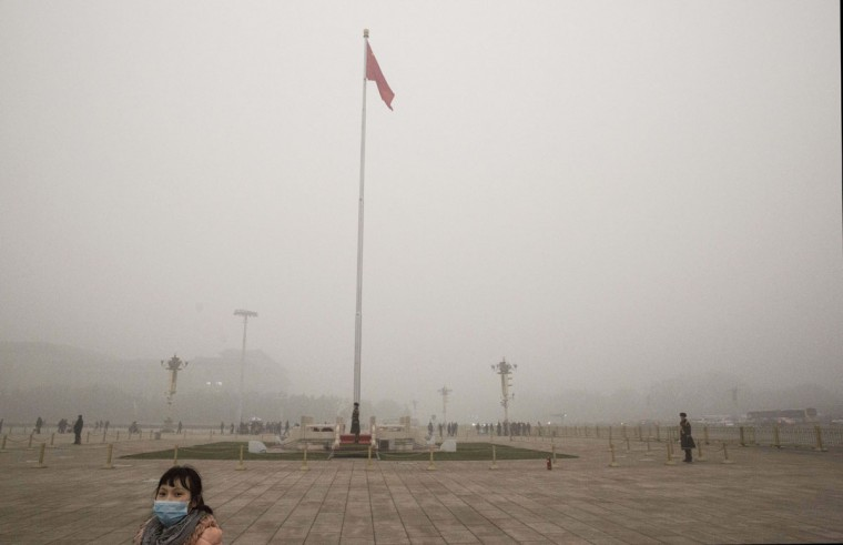 A Chinese tourist wears a mask as she visits Tiananmen Square in heavy smog on a day of high pollution on December 1, 2015 in Beijing, China. (Photo by Kevin Frayer/Getty Images)