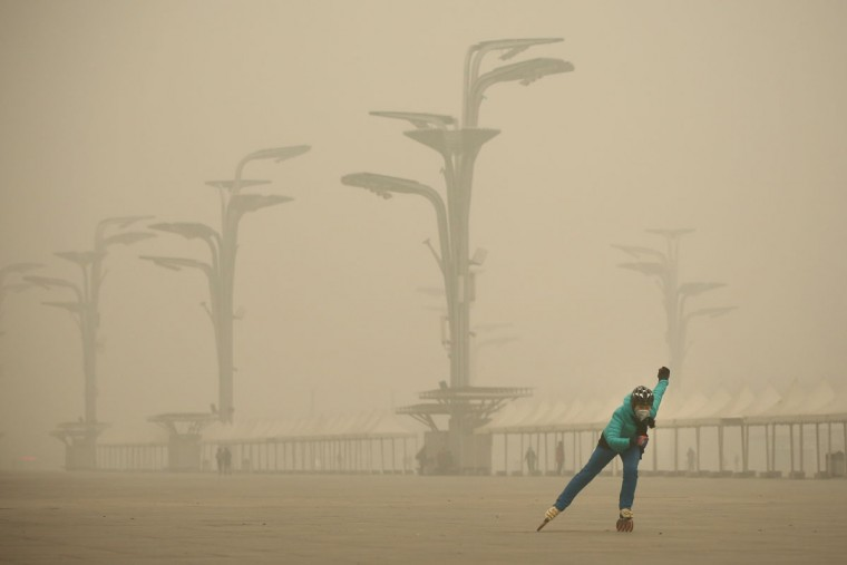 A woman wearing a mask practices roller blading at Olympic Park during dheavy smog on December 1, 2015 in Beijing, China. (Photo by Feng Li/Getty Images)