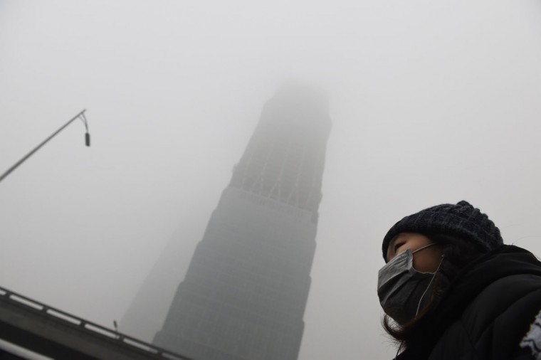 A woman waits for a bus below a skyscraper shrouded in smog on a heavily polluted day in Beijing on December 1, 2015. (GREG BAKER/AFP/Getty Images)