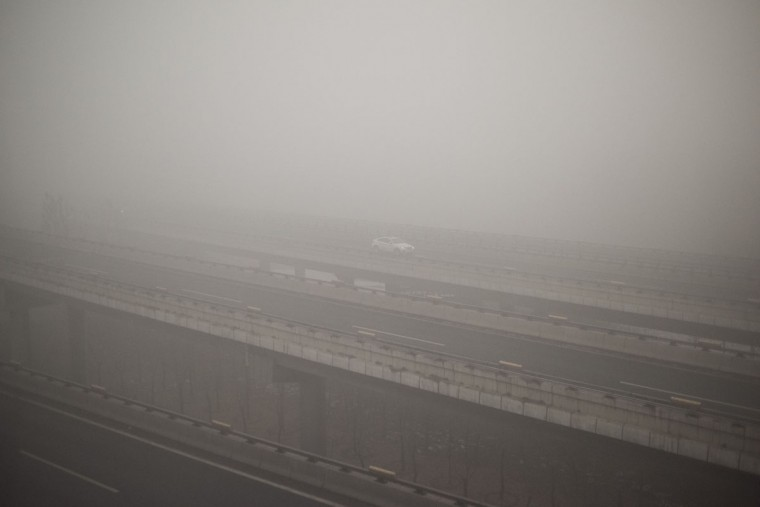 A car drives along a highway on a polluted day in Beijing on December 1, 2015. (FRED DUFOUR/AFP/Getty Images)
