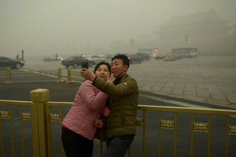 A couple take a selfie near Tiananmen Square during heavy pollution in Beijing on December 1, 2015. Beijing ordered hundreds of factories to shut and allowed children to skip school as choking smog reached over 25 times safe levels on December 1, casting a cloud over China's participation in Paris climate talks. (WANG ZHAO/AFP/Getty Images)
