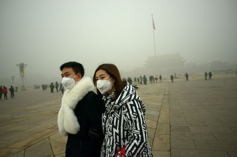 A couple wear masks as they walk in Tiananmen Square during heavy pollution in Beijing on December 1, 2015. (WANG ZHAO/AFP/Getty Images)