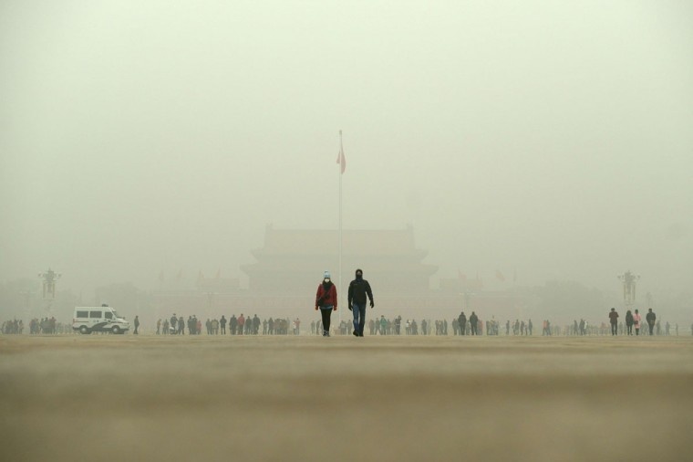 A man and a woman wear masks as they walk in Tiananmen Square during heavy pollution in Beijing on December 1, 2015. (WANG ZHAO/AFP/Getty Images)