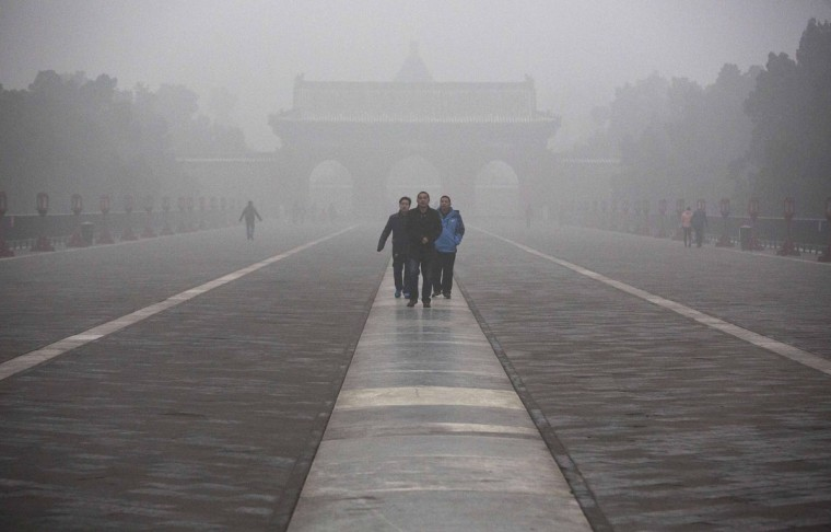 Chinese tourists walk on a high pollution day in the Temple of Heaven on December 1, 2015 in Beijing, China. (Photo by Kevin Frayer/Getty Images)