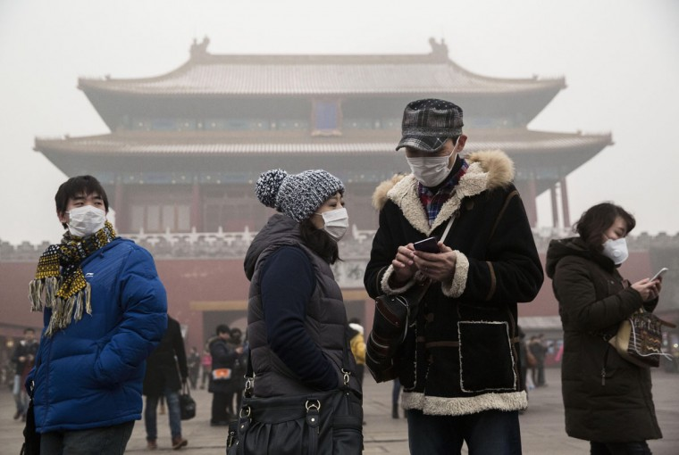 Chinese tourists wear masks as protection from the pollution outside the Forbidden City during a day of high pollution on December 1, 2015 in Beijing, China. (Photo by Kevin Frayer/Getty Images)