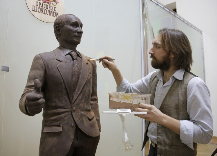 Sculptor Nikita Gusev corrects his life-sized chocolate statue of Russian President Vladimir Putin prior the opening the Chocolate Festival in St.Petersburg, Russia, Saturday, Dec. 5, 2015. The life-sized chocolate sculpture was created by Russian artist Nikita Gusev.(AP Photo/Dmitry Lovetsky)