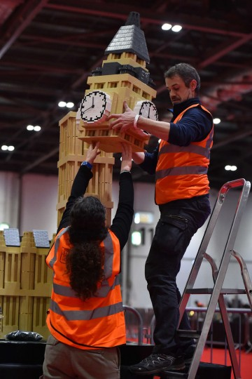 An exhibitor puts the finishing touches to a model of the Houses of Parliament's Elizabeth Tower (Big Ben) made from Lego for the Brick 2015 exhibition at the ExCel in London on December 10, 2015. (BEN STANSALL/AFP/Getty Images)
