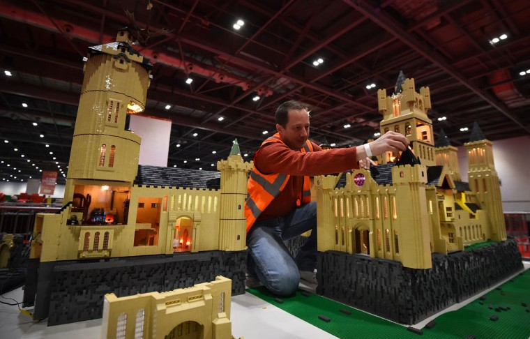 An exhibitor puts the finishing touches to a model of the school from the Harry Potter novels 'Hogwarts' made from Legos for the Brick 2015 exhibition at the ExCel in London on December 10, 2015. (BEN STANSALL/AFP/Getty Images)