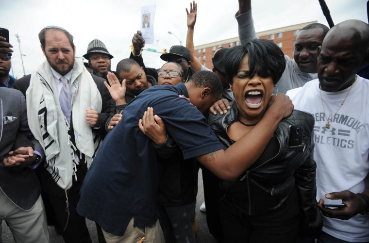 Rev. Pamela Coleman (right) prays with Baltimore residents at the corner of West North Avenue and Pennsylvania Avenue after charges were brought against six Baltimore police officers in the death of Freddie Gray. (Kim Hairston/Baltimore Sun)