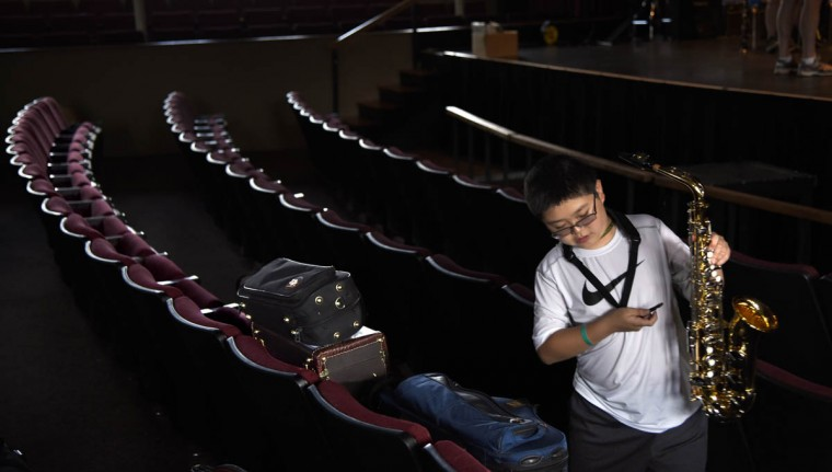 Justin Hsieh, 12 of Ellicott City, walks with his alto saxophone toward the rehearsal hall stage at the 30th annual summer music camp for middle and high school students on the campus of McDaniel College. (Barbara Haddock Taylor, Baltimore Sun)