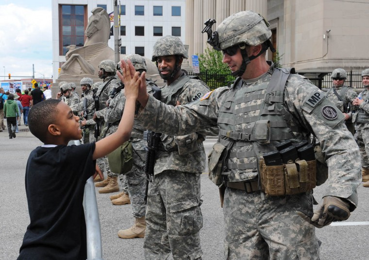 Asad Ali, 9, of Washington, DC, gives a high-five to Sgt 1st Class Joe Hatcher with the Maryland National Guard during Saturday's rally at War Memorial Plaza. (Jerry Jackson, Baltimore Sun)