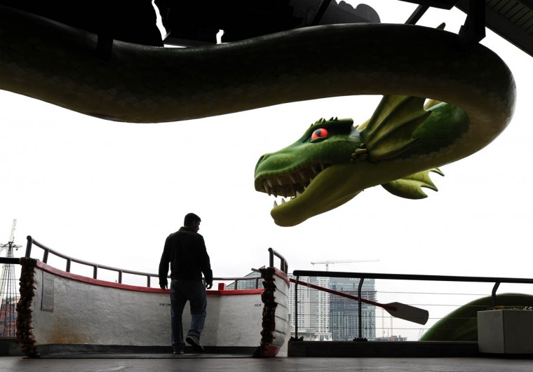 Eric Beglan of Owings Mills enjoys a day at the Inner Harbor as the serpent from the Ripley's Believe it or Not looms overhead. (Lloyd Fox/Baltimore Sun)