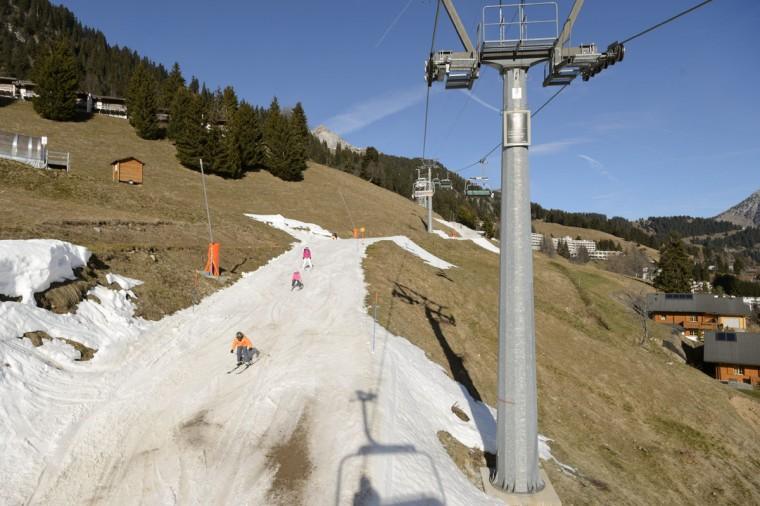 People ski on a slope covered with artificial snow surrounded by green fields in the Swiss Alps in Leysin, Switzerland, on Thursday Dec.; 24, 2015. (Laurent Gillieron/Keystone via AP)