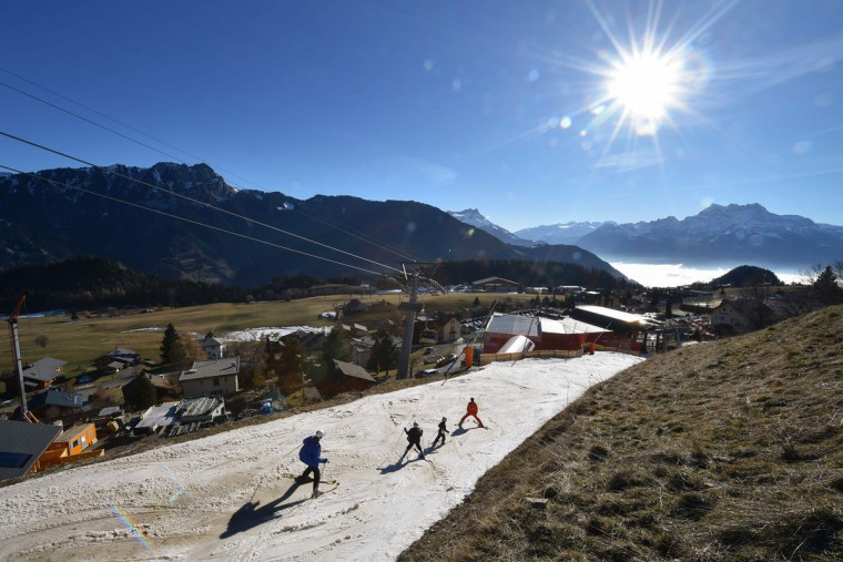 Tourists ski on a thin layer of snow towards the resort of Leysin, Swiss Alps, on December 28, 2015. (FABRICE COFFRINI/AFP/Getty Images)