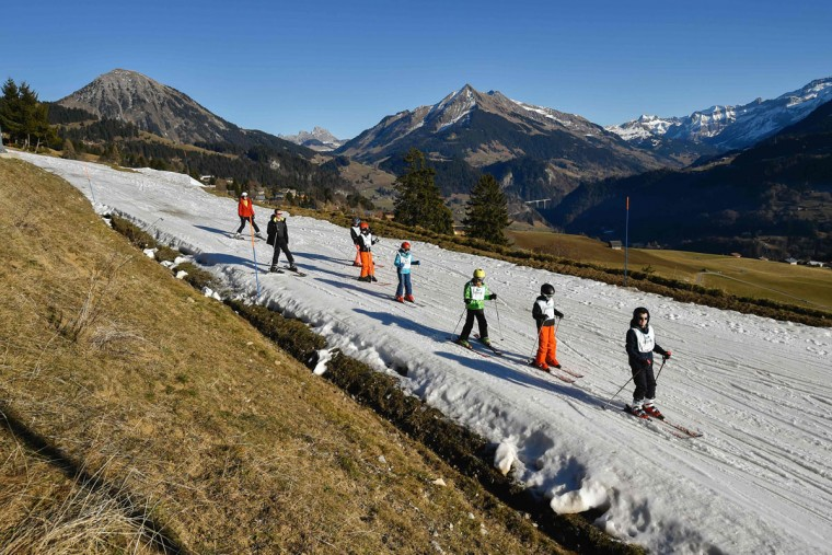 Children from ski schools practice on a thin layer of snow near the resort of Leysin, Swiss Alps, on December 28, 2015. (FABRICE COFFRINI/AFP/Getty Images)